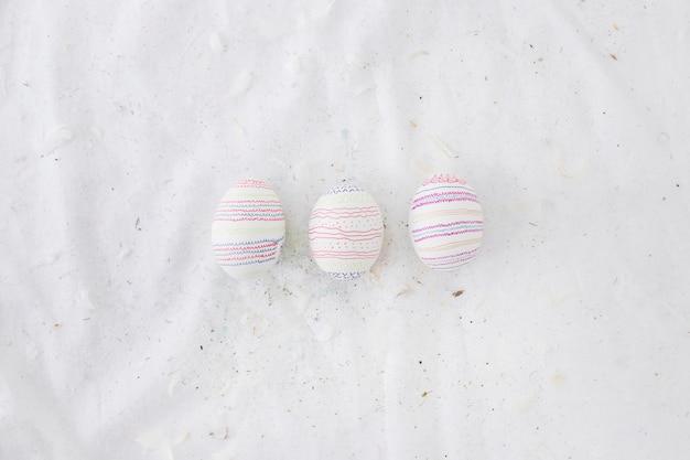 Set di uova di pasqua con motivi e piume sul tessile
