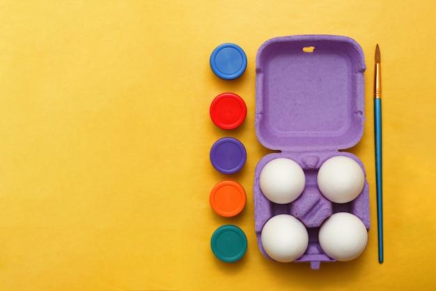 Set di uova di pasqua e vasetti di vernice e pennelli