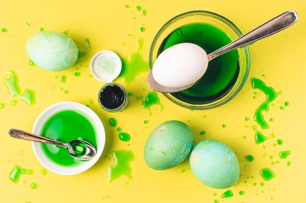 Set di uova di pasqua verdeggianti tra macchie, cucchiaio e liquido di tintura