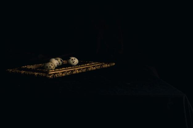 Set di uova di quaglia su cornice tra l'oscurità