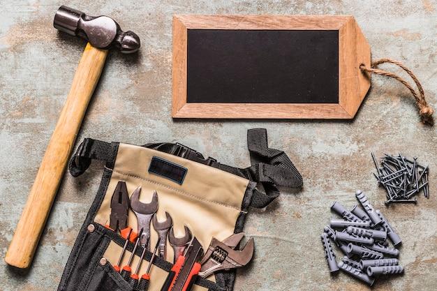 Set di utensili a mano con chiodi e piccola etichetta in ardesia su sfondo grunge
