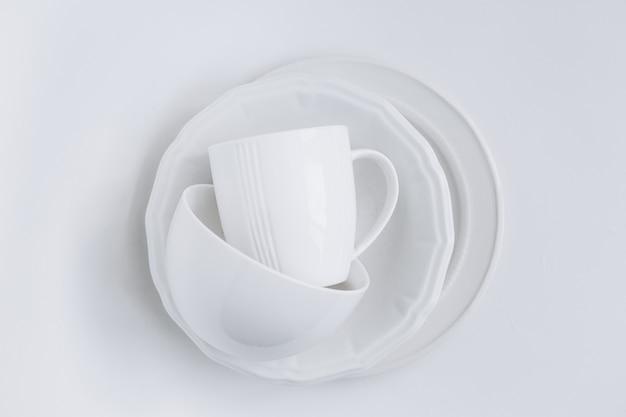 Set di utensili bianchi in una pila di tre piatti diversi e una tazza