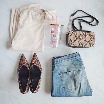 Set di vestiti di moda donna. elegante pochette a mano serpente, scarpe alla moda leopardate. piatto giaceva su sfondo bianco