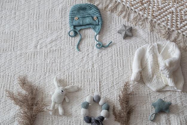 Set di vestiti lavorati a maglia fatti a mano alla moda per bambini con vari accessori in stile boho, vista dall'alto.