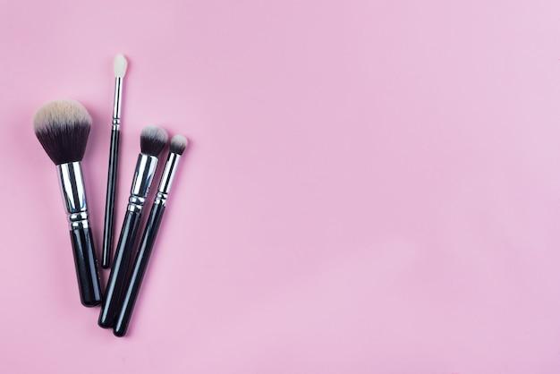 Set di vista superiore piatta di vari cosmetici femminili professionali pennelli per il trucco