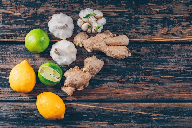 Set di zenzero, aglio e limoni verdi e gialli su un fondo di legno scuro. disteso.