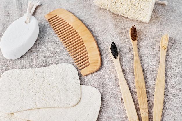 Set naturale per il bagno di spazzolini da denti in bambù, luffa spongle e spazzola per capelli in legno su uno sfondo di lino.