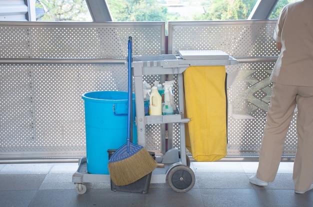Set sanitario sul vassoio con uomo delle pulizie, bottiglia di liquido per l'igiene con mocio e fiore e cestino per area pubblica pulita.