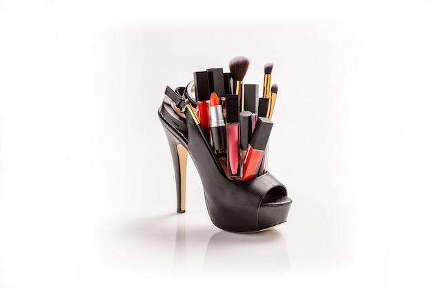 Set trucco con scarpa da donna nera, pennelli e cosmetici