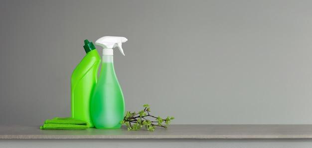 Set verde per pulizie primaverili e qualche rametto con foglie giovani di primavera.