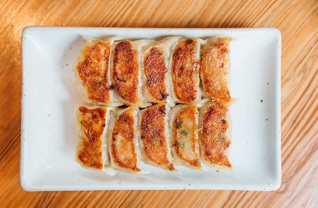 Set yaki-gyoza (gnocchi pan-fritti giapponesi) servito su piatto bianco.