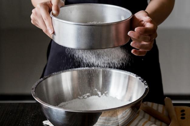 Setacciare la farina attraverso un setaccio