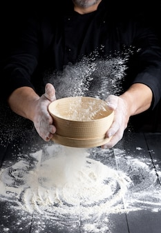 Setaccio rotondo in legno con farina in mani maschili