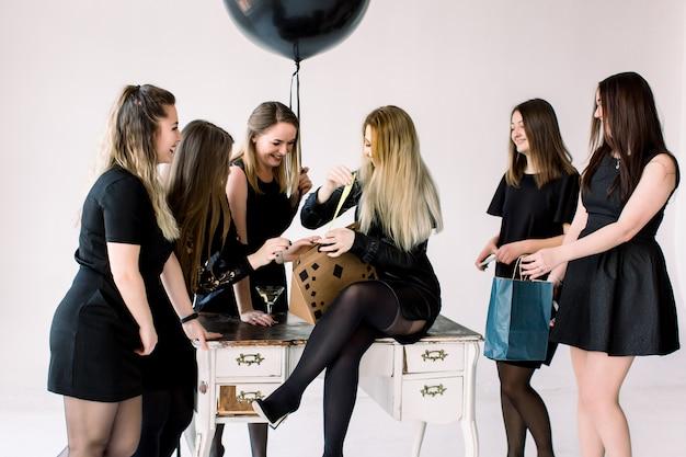 Sette belle giovani donne celebrano addio al nubilato e divertirsi su sfondo bianco. le migliori amiche che indossano un elegante abito da sera nero che celebrano la festa di compleanno
