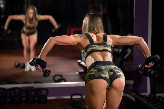Sexy bel culo in perizoma. donna atletica che pompa i muscoli con le teste di legno nel club di forma fisica. la retrovisione di giovane femmina che fa si esercita in palestra.