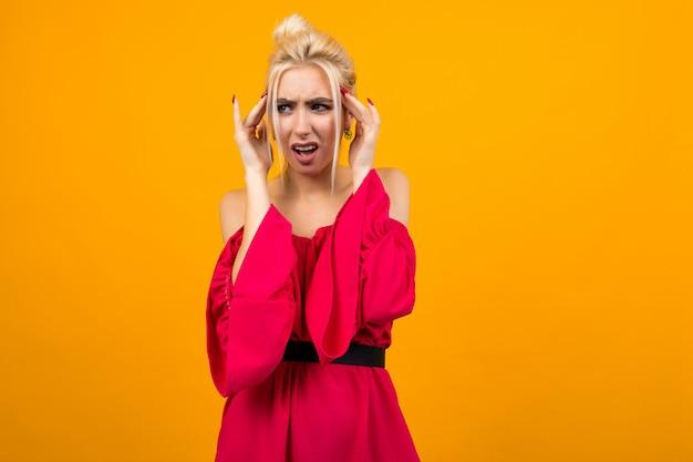 Sexy eccitata ragazza bionda affascinante in abito rosso si copre le orecchie con le mani sul muro giallo