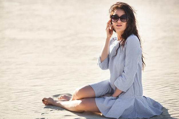 Sexy giovane donna nel deserto. bella ragazza sulla sabbia