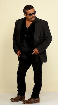 Sexy indiano bello con i baffi che indossa abito nero