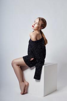 Sexy ragazza bionda in maglione seduto, trucco vivido