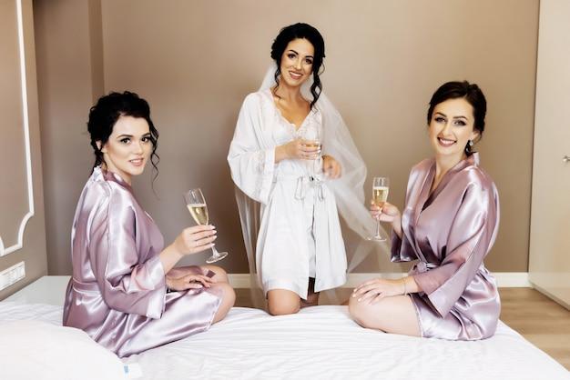 Sexy sposa e damigelle che saltano sul letto prima del matrimonio