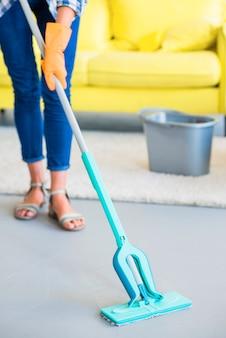 Sezione bassa del custode femminile che pulisce il pavimento con la scopa