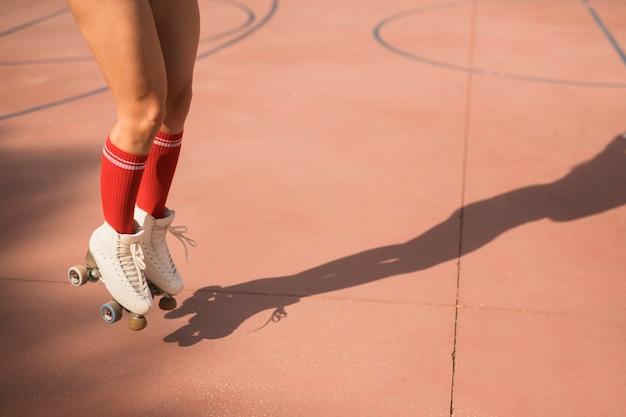 Sezione bassa del pattinatore femminile che salta in aria sulla corte