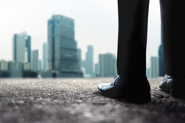 Sezione bassa dell'uomo d'affari in piedi sul tetto con molti edifici urbani