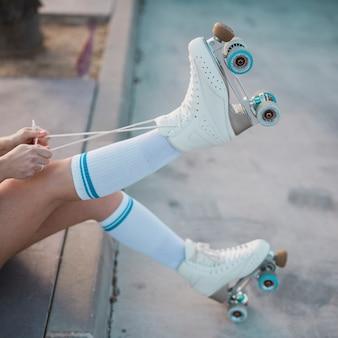 Sezione bassa della donna che lega il merletto del pattino a rotelle sulla strada
