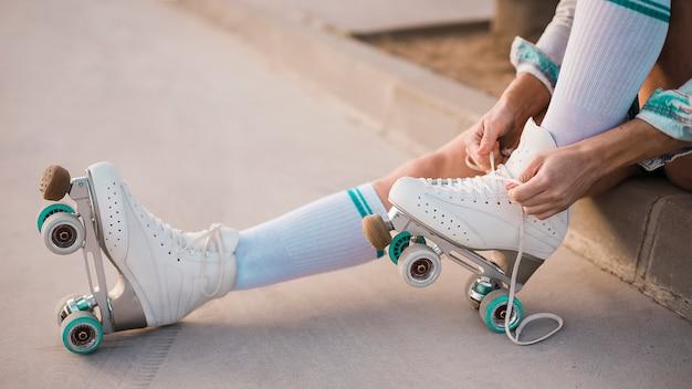 Sezione bassa della donna che lega il merletto del pattino a rotelle