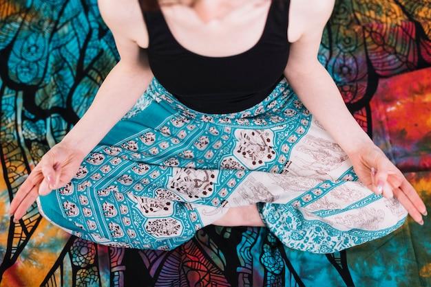 Sezione bassa della donna che si siede nella posa del loto con il gesto di mudra sulla coperta