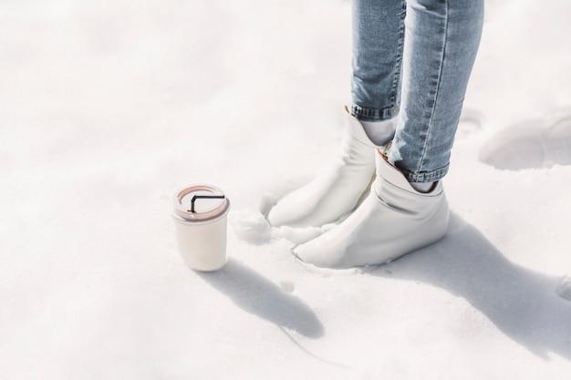 Sezione bassa della donna con la tazza di caffè asportabile che sta sulla neve