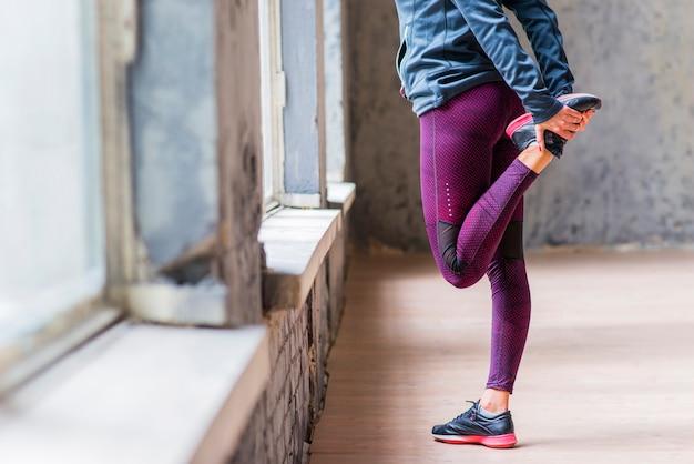 Sezione bassa della donna in piedi su una gamba che si estende la gamba