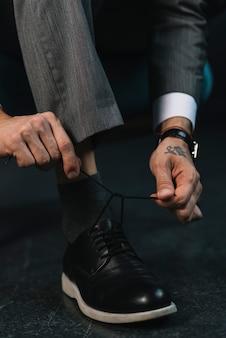 Sezione bassa della mano dell'uomo d'affari che lega il laccetto