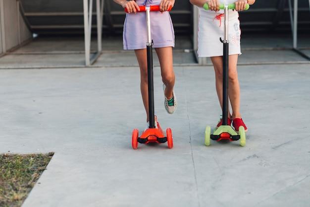 Sezione bassa di due ragazze in piedi sul loro scooter
