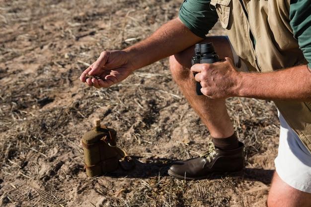 Sezione bassa di fango della holding dell'uomo sul campo