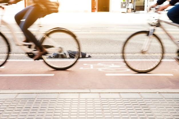 Sezione bassa di persone in sella alla bicicletta in pista ciclabile
