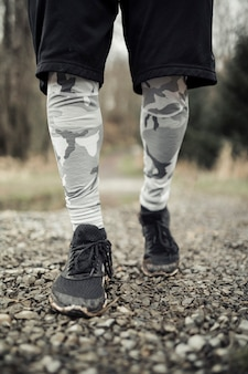 Sezione bassa di scarpe runner maschio su sentiero di ghiaia