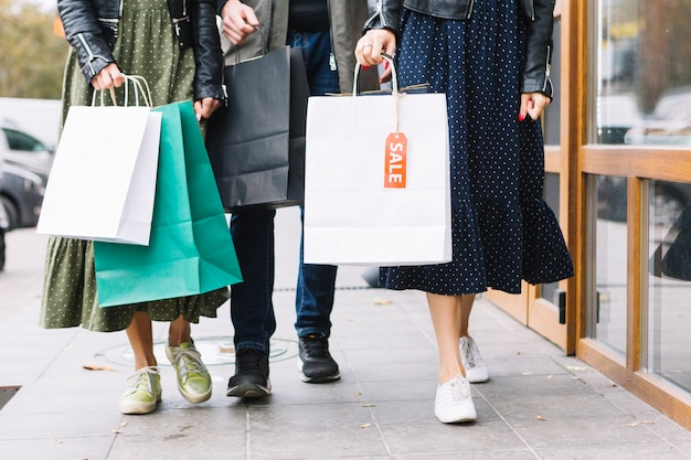 Sezione bassa di un amici che camminano sul marciapiede con borse della spesa colorate