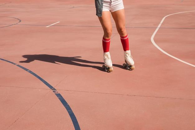 Sezione bassa di un pattinatore femminile che pattina su un campo all'aperto
