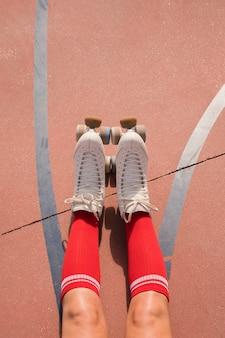 Sezione bassa di una pattinatrice con calzini rossi e pattini a rotelle