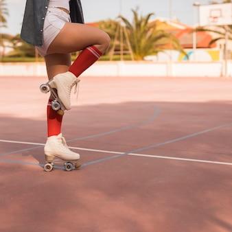 Sezione bassa di una pattinatrice in piedi su una gamba sopra la corte