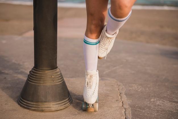 Sezione bassa di una pattinatrice in piedi su una gamba vicino al pilastro