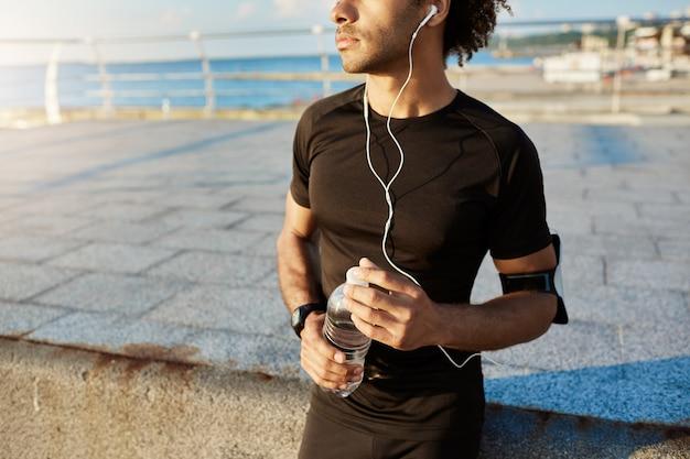 Sezione mediana del corridore maschio dalla pelle scura in abiti sportivi neri che tiene una bottiglia di acqua minerale nelle sue mani, utilizzando l'app musicale sul cellulare durante l'allenamento da jogging dietro il mare.