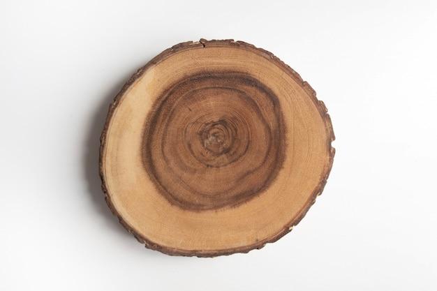 Sezione trasversale del ceppo di albero sulla tavola bianca