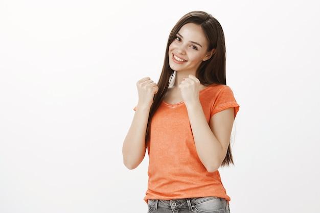 Sfacciata e civettuola bella ragazza shadowboxing, alzando le mani come un pugile