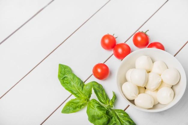 Sfera del formaggio della mozzarella con la foglia del basilico e pomodori rossi su fondo bianco di legno