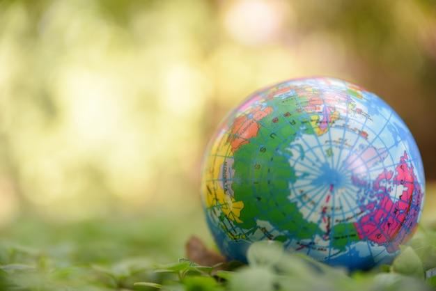 Sfera del globo sulle foglie verdi naturali a terra e sul fondo verde del bokeh. concetto di giornata mondiale dell'ambiente.