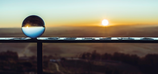 Sfera di cristallo sulla ringhiera che riflette il cielo e il sole dell'alba