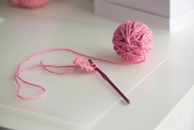 Sfera di filato rosa con filo di lana su bianco