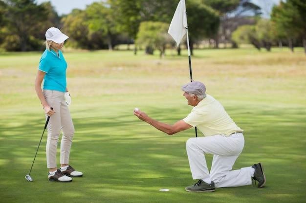 Sfera di golf matura della holding dell'uomo dalla donna